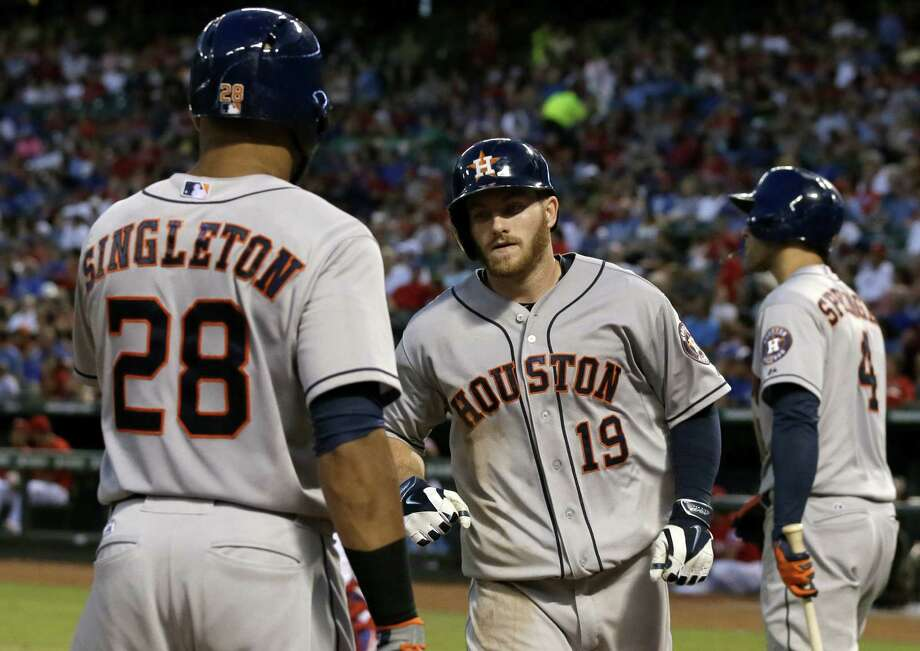 The Astros' Robbie Grossman (19) is greeted by Jon Singleton after hitting a solo home run off Texas' Yu Darvish in the fifth inning. George Springer (background) also homered in the win. Photo: Tony Gutierrez / Associated Press / AP
