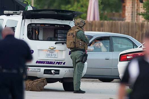 Law enforcement officers surround a shooting suspect in his car Wednesday, July 9, 2014, in Spring. Seven people were shot, with six confirmed dead. ( Brett Coomer / Houston Chronicle ) Photo: Brett Coomer, Staff / © 2014 Houston Chronicle