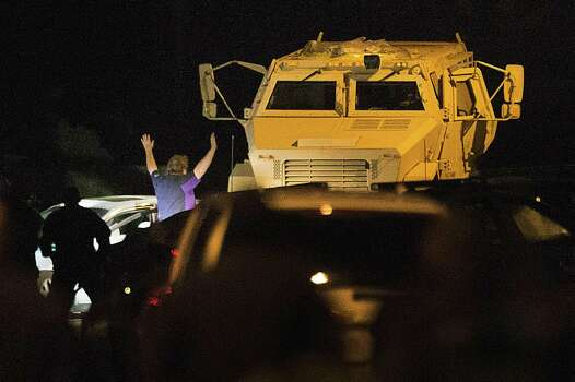 A shooting suspect surrenders Wednesday night in Spring after a lengthy standoff in which his car was hemmed in by a pair of armored vehicles. Photo: Brett Coomer, Staff / © 2014 Houston Chronicle