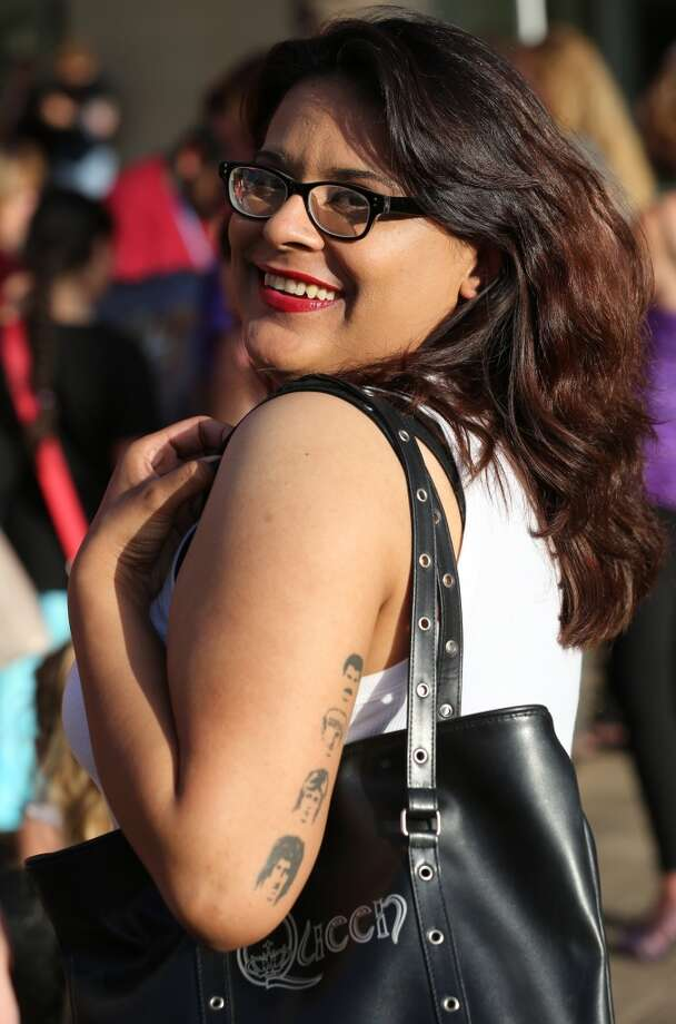 "Brandy Huston shows off her tattoos honoring Queen as she and other fans wait outside Toyota Center before the show on July 9. The rockers performed with former ""American Idol"" star Adam Lambert. Photo: Thomas B. Shea, For The Houston Chronicle"