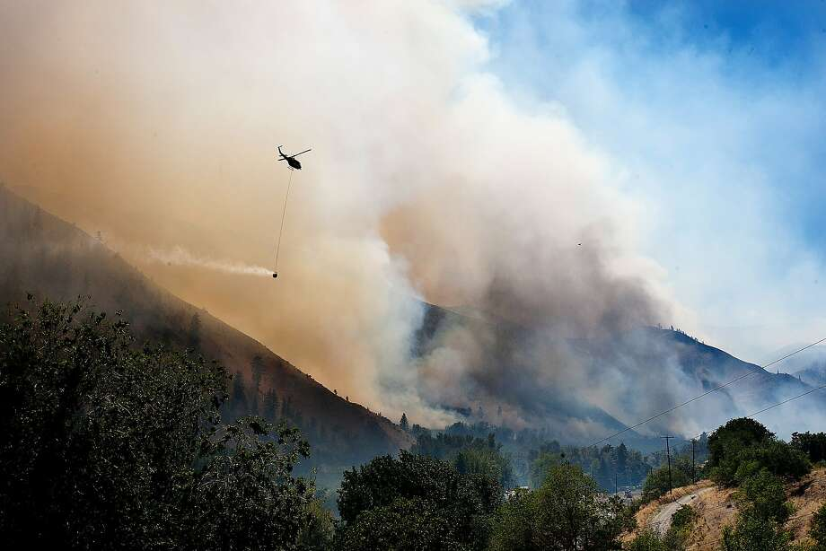 As smoke and fire blow through the lower Entiat Valley near Entiat, Wash., on Wednesday afternoon, July 9, 2014, a helicopter with a bucket of water flies to the fire to drop its load. Fire spokesman Mick Mueller says about 250 firefighters were aided by air tankers dropping retardant and helicopters dropping water on the fire. Several dozen homeowners have been warned they might need to evacuate.  Photo: Don Seabrook, Associated Press