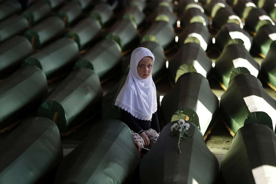 Ema Hasanovic, 5, a young Bosnian Muslim girl, pays her respects near to the coffin of her uncle, in the Memorial center in Potocari, 200 kms northeast of Sarajevo, on Wednesday, July 9, 2014. Hundreds of people turned out in Sarajevo's main street to pay their respects to 175 victims of the Srebrenica massacre — Europe's worst since World War II — as a truck carried their coffins to a final resting place. The remains of the men and boys, found in mass graves and identified through DNA analysis, will be buried in Srebrenica on Friday, the 19th anniversary of the massacre, next to 6,066 previously found victims. (AP Photo/Amel Emric) Photo: Ap, Associated Press