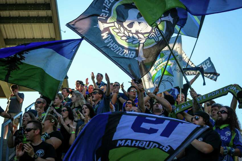 Seattle Sounders FC fans wave flags during the Lamar Hunt U.S. Open Cup Quarterfinals match between Seattle Sounders FC and the Portland Timbers on Wednesday, July 9, 2014. The Sounders won the match 3-1.