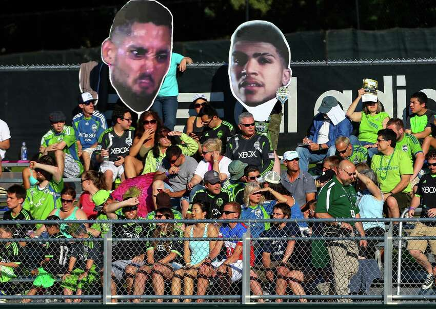 Fans hold up giant Clint Dempsey and DeAndre Yedlin heads during the Lamar Hunt U.S. Open Cup Quarterfinals match between Seattle Sounders FC and the Portland Timbers on Wednesday, July 9, 2014. The Sounders won the match 3-1.