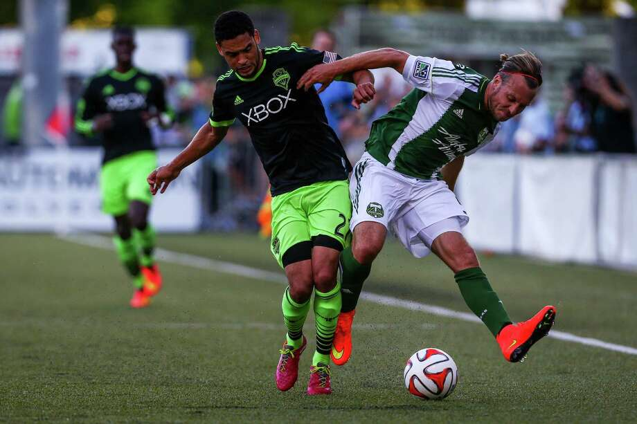 Seattle's Lamar Neagle (left) collides with Portland's Michael Harrington (right) during the Lamar Hunt U.S. Open Cup Quarterfinals match between Seattle Sounders FC and the Portland Timbers on Wednesday, July 9, 2014. The Sounders won the match 3-1. Photo: JOSHUA BESSEX, SEATTLEPI.COM / SEATTLEPI.COM