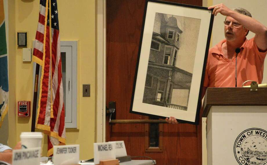 Matthew Mandell, a member of the Kemper-Gunn Advisory Committee and Chamber of Commerce executive director, displays for finance board members a picture of the Kemper-Gunn House that he pulled off the wall in the Town Hall lobby to illustrate a point Wednesday night. Photo: Jarret Liotta / Westport News
