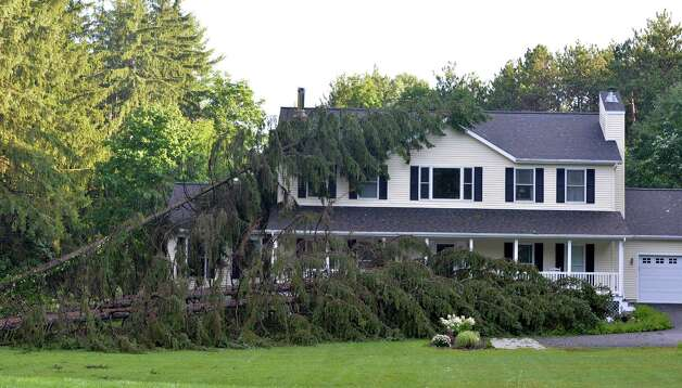 Three large pine trees lay on a home at 2633 New Scotland Road Thursday morning, July 10, 2014, in New Scotland, N.Y. A fast moving storm swept through the region Wednesday evening causing flooding and damage. (Skip Dickstein/Times Union)