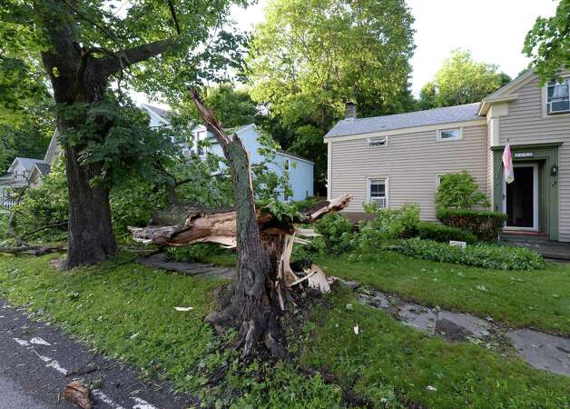 A shattered tree lies on a home at 2680 New Scotland Road Thursday morning, July 10, 2014, in New Scotland, N.Y. A fast moving storm swept through the region Wednesday evening causing flooding and damage. (Skip Dickstein/Times Union)