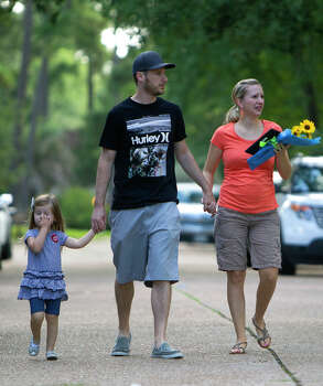 Friends of a family of seven people who were shot walk to leave flowers and a framed photo at the home, Thursday, July 10, 2014, in Spring. The shooting took place Wednesday killing six people including four children and two adults, who were shot to death after an apparent domestic dispute. Photo: Cody Duty, Houston Chronicle / © 2014 Houston Chronicle