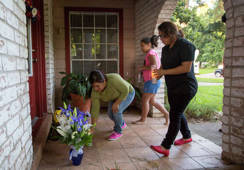 Elvia Palacios, left, Anamari Palacios, 11, center, Viridiana Palacios, place candles on the front of a home where seven people were shot, Thursday, July 10, 2014, in Spring. The shooting took place Wednesday killing six people including four children and two adults, who were shot to death after an apparent domestic dispute. Photo: Cody Duty, Houston Chronicle / © 2014 Houston Chronicle