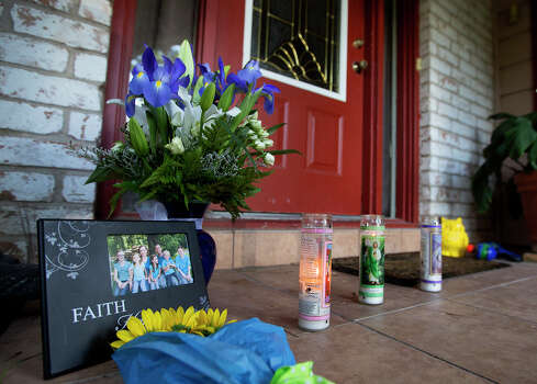 A framed photo, along with flowers and candles, is seen in front of the home where seven people were shot, Thursday, July 10, 2014, in Spring. The shooting took place Wednesday killing six people including four children and two adults, who were shot to death after an apparent domestic dispute. Photo: Cody Duty, Houston Chronicle / © 2014 Houston Chronicle