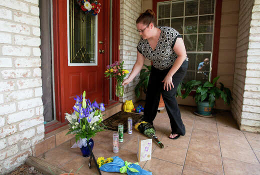 Kristen Breedlove places flowers in the front of the home where seven people were shot, Thursday, July 10, 2014, in Spring. The shooting took place Wednesday killing six people including four children and two adults, who were shot to death after an apparent domestic dispute. Photo: Cody Duty, Houston Chronicle / © 2014 Houston Chronicle