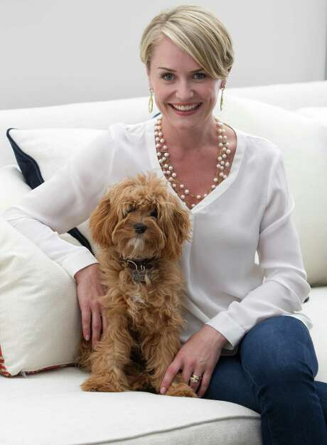 Julie Rhodes poses for a portrait with her 7-month-old cavapoo Betty at her boutique on Monday, July 7, 2014, in Houston. ( J. Patric Schneider / For the Chronicle ) Photo: J. Patric Schneider, Freelance / © 2014 Houston Chronicle