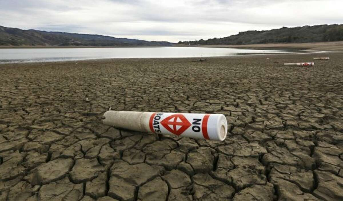 In this file photo, a warning buoy sits on the dry, cracked bed of Lake Mendocino near Ukiah, Calif. The Legislature has placed a  $7.5 billion water bond measure that is scheduled to go before voters in November.