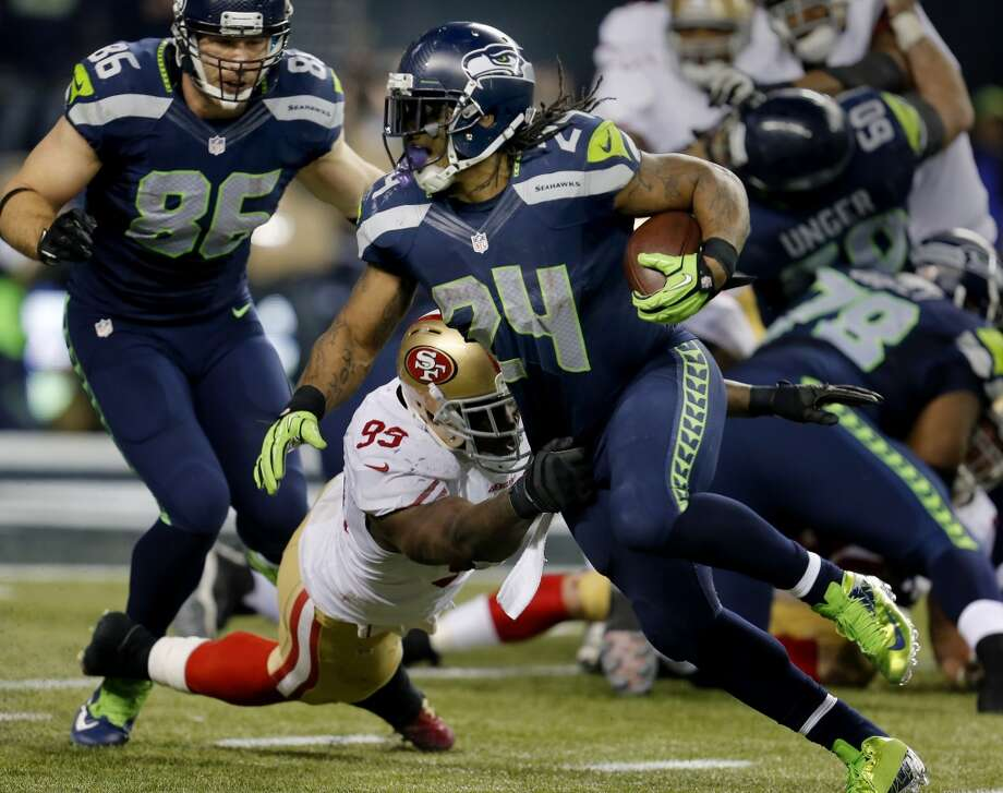 Seattle's Marshawn Lynch (24) eludes a tackle from the 49ers Aldon Smith (99) in the fourth quarter Sunday January 19, 2014. The Seattle Seahawks defeated the San Francisco 49ers 23-17 to win the NFC championship and a trip to the Super Bowl at CenturyLink Field in Seattle, Washington. Photo: Brant Ward, The Chronicle