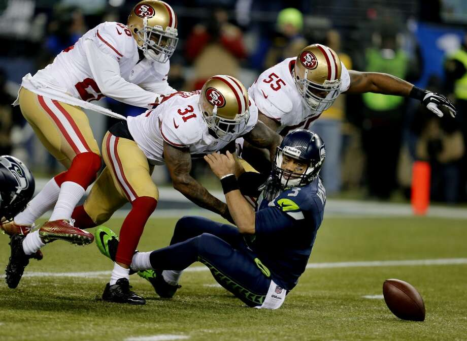 Seattle's Russell Wilson (3) loses the ball as they tried to convert on a fourth down play in the second half. Donte Whitner (31) and Eric Reid (35) defend Sunday January 19, 2014. The Seattle Seahawks defeated the San Francisco 49ers 23-17 to win the NFC championship and a trip to the Super Bowl at CenturyLink Field in Seattle, Washington. Photo: Brant Ward, The Chronicle