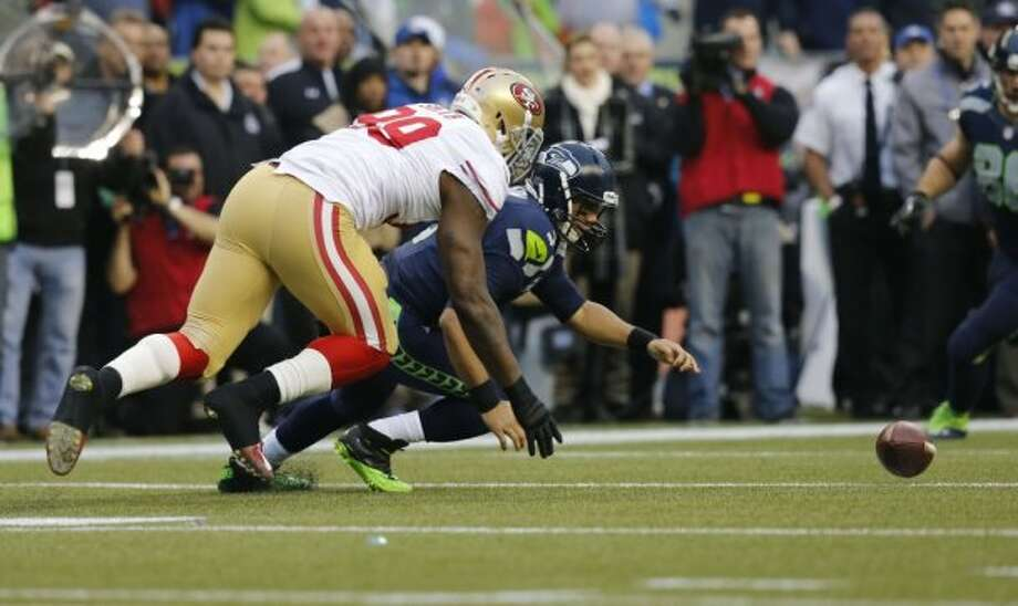 49ers Aldon Smith, (99) forces Seattle quarterback Russell Wilson, (3) to fumble on the first paly of the game, as the San Francisco 49ers take on the Seattle Seahawks in the NFC Championship game at CenturyLink Field in Seattle, Washington on Sunday Jan. 19,  2014. Photo: Michael Macor, The Chronicle
