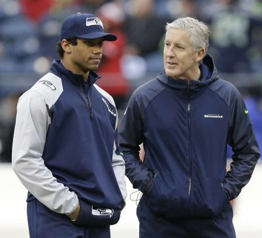 Seattle Seahawks head coach Pete Carroll talks to quarterback Russell Wilson before the NFL football NFC Championship game against the San Francisco 49ers Sunday, Jan. 19, 2014, in Seattle. Photo: Elaine Thompson, Associated Press