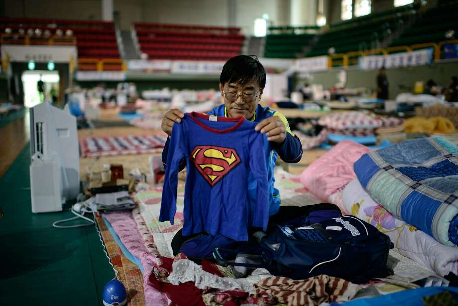 The search for the last victims:Kwon Oh-Bok, whose 6-year-old nephew was aboard the Sewol ferry that sank in April and is still unaccounted for, holds a Superman   t-shirt recovered from the ferry inside a Jindo, South Korea, gymnasium. As divers continued the dangerous search for the last remaining bodies (293 have been recovered so far), South Korean investigators revealed that the ferry was licensed based on falsified documents and carrying double its cargo limit when it capsized. Photo: Ed Jones, AFP/Getty Images