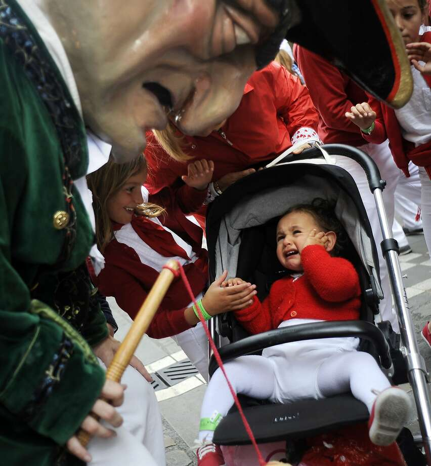In Pamplona, the Running of the Bulls and the Scaring of the Small Children continues:A baby cries upon meeting a cabezudo (big head) during the San Fermin festivals. Photo: Rafa Rivas, AFP/Getty Images