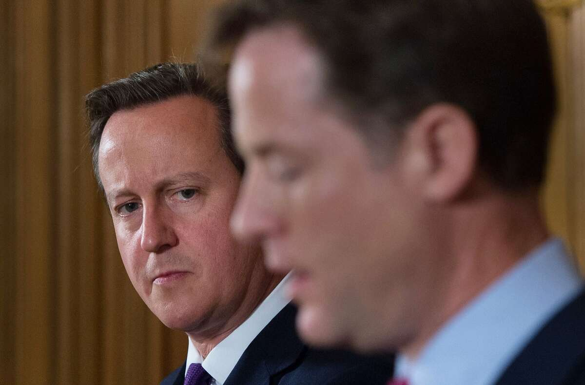 Britain's Prime Minister David Cameron, background pauses as Deputy Prime Minister Nick Clegg speaks, during a news conference, at 10 Downing Street in London, Thursday July 10, 2014. Britain's prime minister pledged Thursday to rush through new measures to give police and spy agencies the power to scoop up mobile phone and Internet data. Prime Minister Dave Cameron argued that the emergency bill was necessary because of a European Court of Justice ruling that expressed concern about wholesale pickup and use of data. (AP Photo/Stefan Rousseau, Pool)