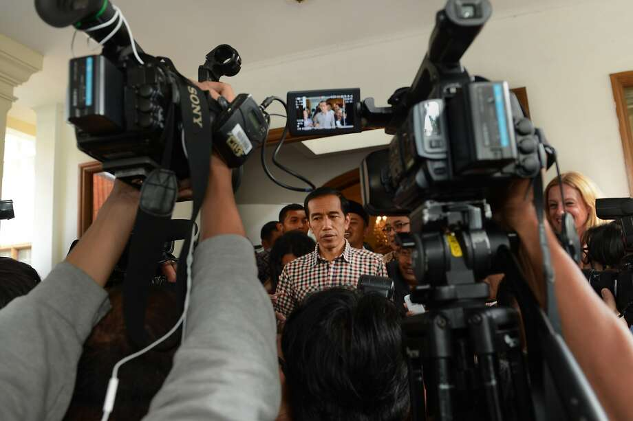 Indonesian presidential candidate Joko Widodo (C) speaks to journalists after a press conference in Jakarta on July 10, 2014. Both sides claimed victory on July 9, 2014 in Indonesia's tightest and most divisive presidential election since the end of authoritarian rule, as most unofficial tallies showed Jakarta governor Joko Widodo leading over ex-general Prabowo Subianto. AFP PHOTO / ROMEO GACADROMEO GACAD/AFP/Getty Images Photo: Romeo Gacad, AFP/Getty Images