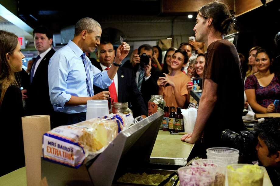 President Barack Obama scrutinizes his credit card as he jokes with the wait staff while ordering barbecue at Franklin Barbecue in Austin, Texas, Thursday, July 10, 2014. Austin is the final leg in his three city trip before returning to Washington. (AP Photo/Jacquelyn Martin) Photo: Jacquelyn Martin, Associated Press / AP