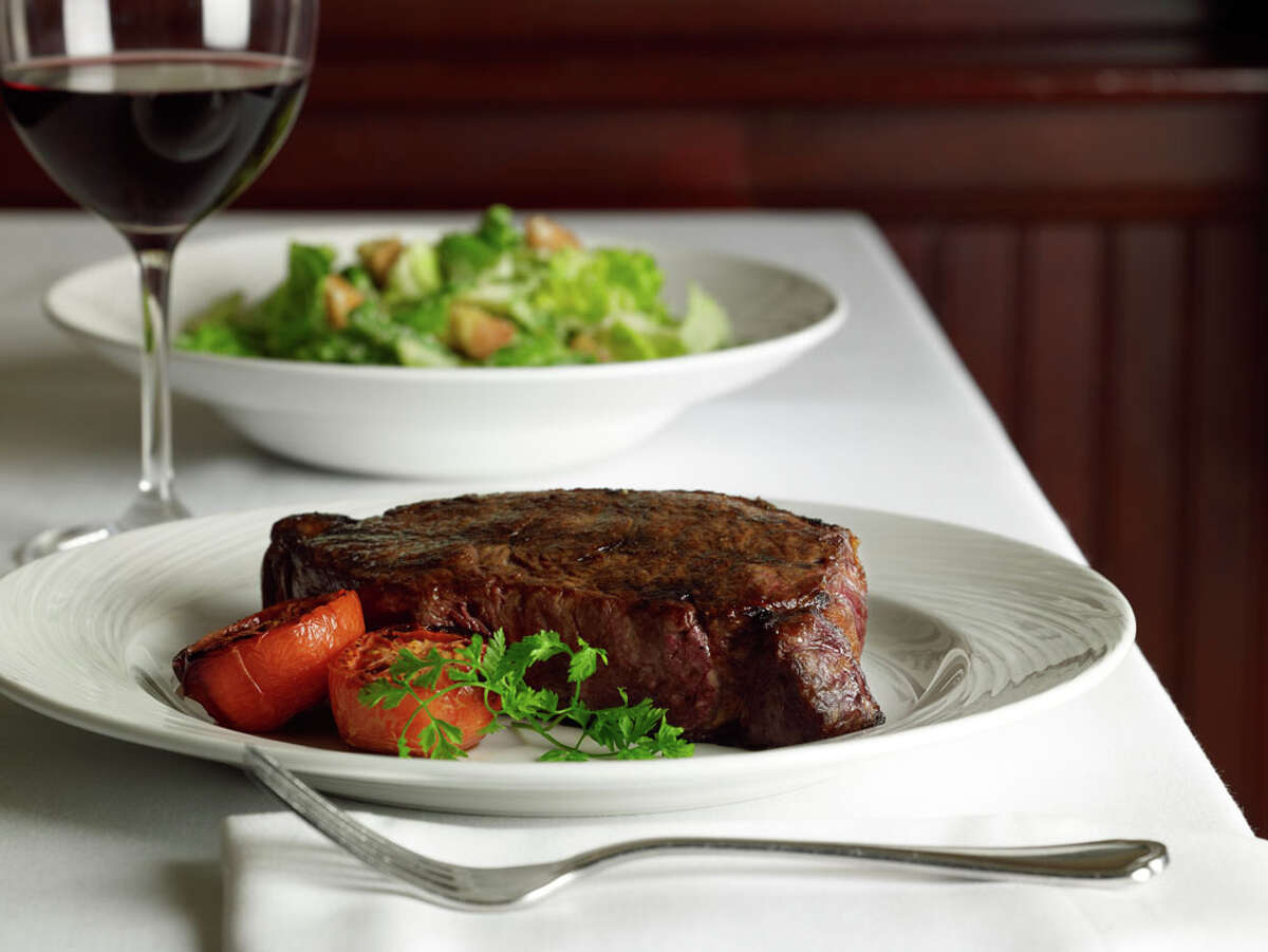 Prime New York strip steak and salad at The Palm steakhouse.
