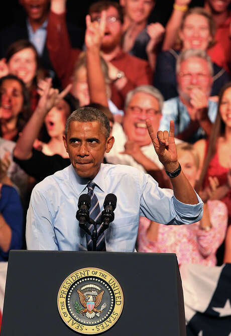 President Barack Obama flashes the Hook'em Horns sign before delivering his remarks at the Paramount Theatre in Austin, Thursday, July 10, 2014. Photo: Jerry Lara, San Antonio Express-News / @San Antonio Express-News