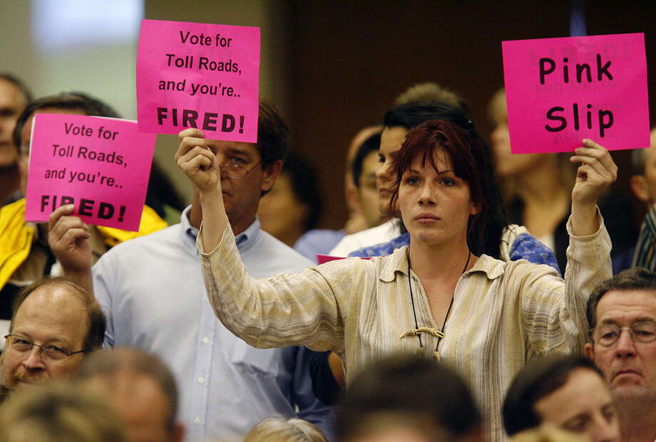 A woman holds up a pair of signs to express her opposition to a proposal to create toll roads along U.S. 281. The occasion was a 2009 meeting of the Metropolitan Planning Organization. Photo: Express-News File Photo / sdulai@express-news.net