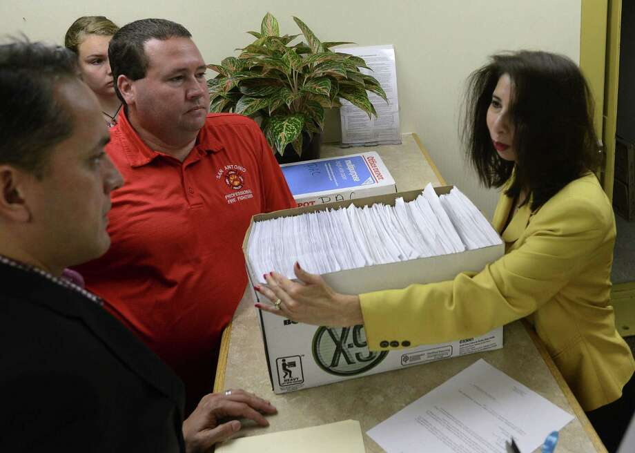 Greg Brockhouse (left) and Stephen Moody deliver petitions to the city clerk's office Tuesday as part of an ongoing effort to put the rail project to a vote. Photo: Billy Calzada / San Antonio Express-News / San Antonio Express-News