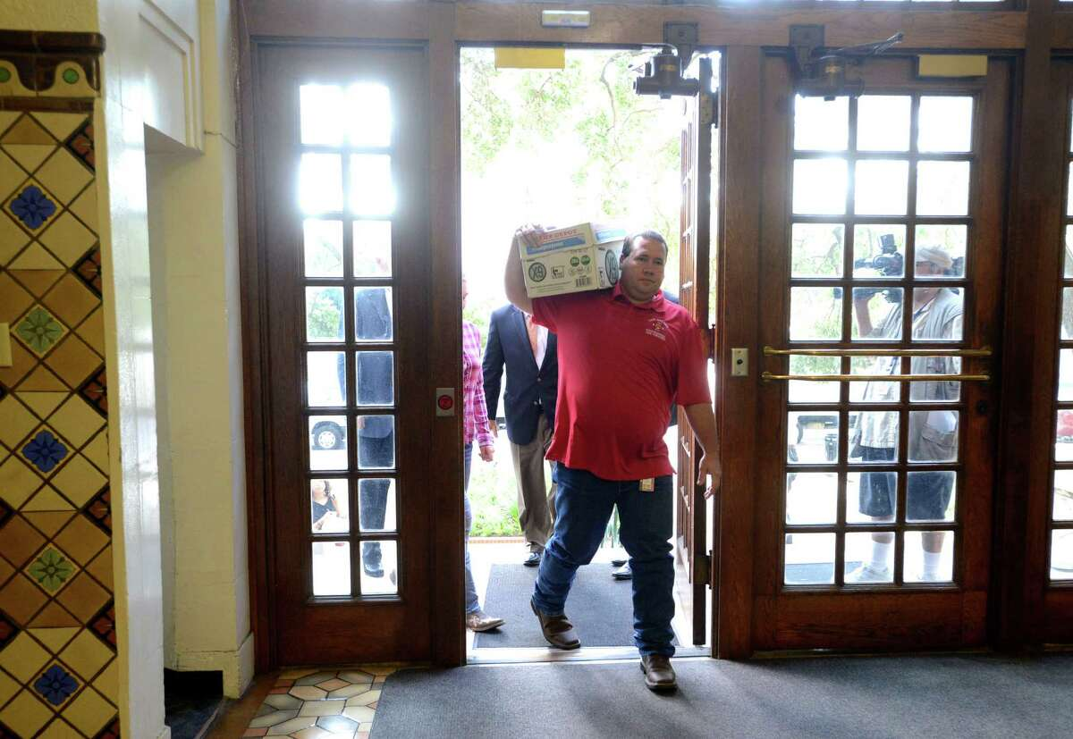 Stephen Moody carries a box containing signatures on petitions to the city clerk's office on Tuesday morning, July 8, 2014.