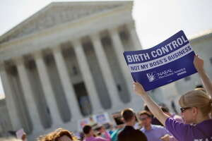 FILE - This June 30, 2014 file photo shows a demonstrator holding up a sign outside the Supreme Court in Washington on the day the court decided in the Hobby Lobby case to relieve businesses with religious objections of their obligation to pay for women's contraceptives among a range of preventive services the new health law calls for in their health plans. How much distance from an immoral act is enough is the difficult question behind the next legal dispute over religion, birth control and the new health law that is likely to be resolved by the Supreme Court. The issue in more than four dozen lawsuits from faith-affiliated charities, colleges and hospitals who oppose some or all contraception as immoral is how far the Obama administration must go to accommodate them.  (AP Photo/Pablo Martinez Monsivais, File) ORG XMIT: WX401