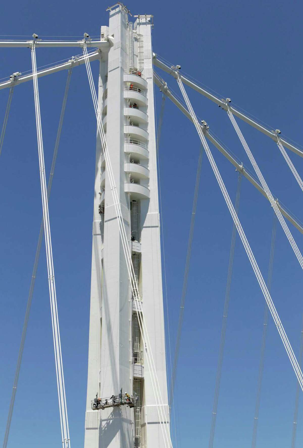 A bridge crew repaints the SAS tower of the new eastern Bay Bridge span from hanging scaffolding in San Francisco, Calif. on Thursday, July 10, 2014.