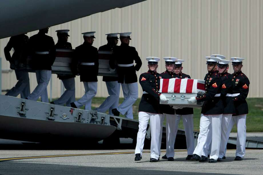 """FILE - This Sept. 14, 2012, file photo shows carry teams at Andrews Air Force Base, Md. moving flag draped transfer cases during the Transfer of Remains Ceremony of the four Americans killed in an attack on a diplomatic outpost and CIA annex Benghazi, Libya. The testimony of nine military officers severely undermines claims by Republican lawmakers that a """"stand-down order"""" held back military assets who could have those killed in the attack.  (AP Photo/Carolyn Kaster, File) Photo: Carolyn Kaster, STF / AP"""
