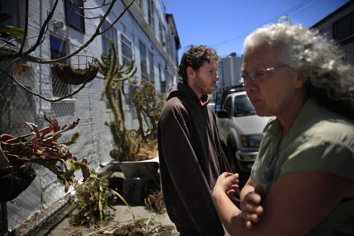 Patty LaCava (right) and her son Nathaniel Galipeau (left) stand near the entrance to the unit in a building in which they lived and from which they were evicted from after a fire on Wednesday, July 2, 2014 in San Francisco, Calif.