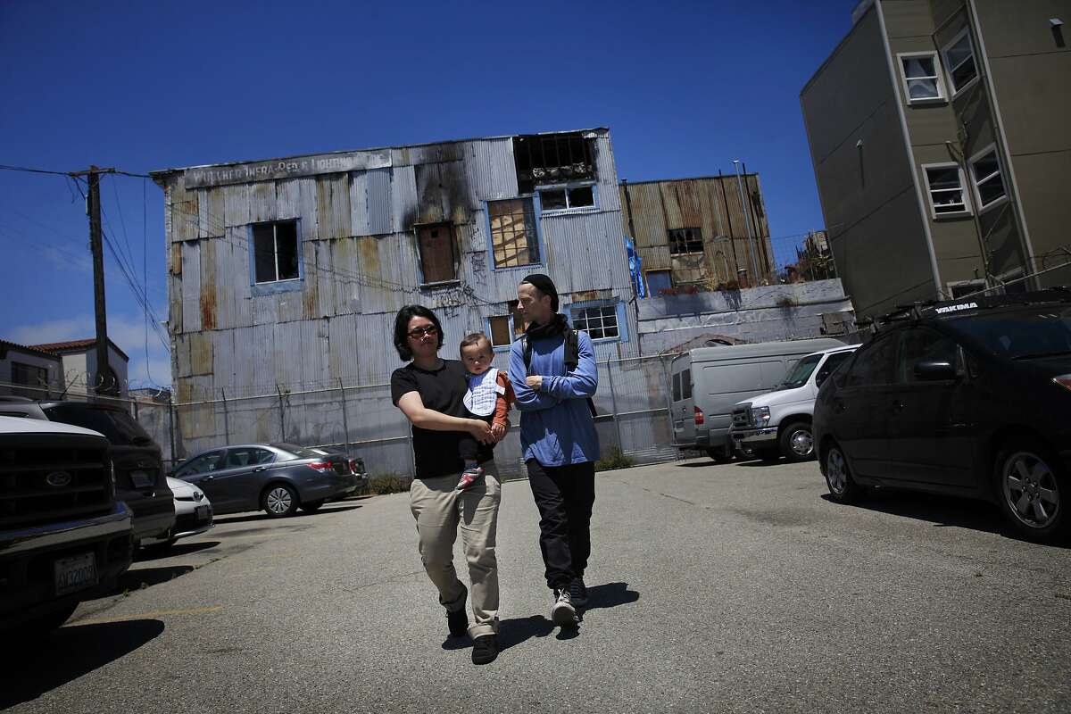 Gibbs Chapman (right) and Katherine Lam (left) walk in front of the building in which they lived with their son Jhun Lee Chapman (center) and were evicted from after a fire on Wednesday, July 2, 2014 in San Francisco, Calif.