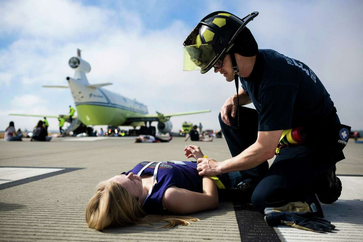 Responders care for nearly 300 victim volunteers at a mock full-scale emergency exercise simulating an aircraft accident Thursday, July 10, 2014, at Sea-Tac International Airport in SeaTac, Wash. The Port of Seattle is organizing region-wide emergency response partners and incorporating lessons learned from last year?•s aircraft incident in San Francisco.