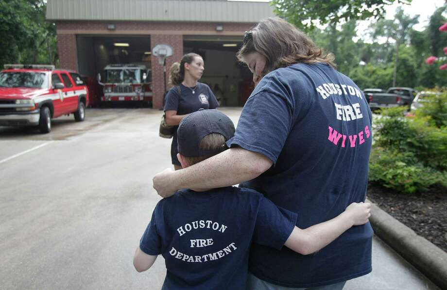 Sarah Tucker, member of the Houston Firefighter Wives Auxiliary group #341, embraces son Luke Tucker, 6, after placing flowers outside HFD Station #104 in honor of veteran firefighter Daniel Groover on July 10, 2014, in Kingwood, Tx. Photo: Mayra Beltran, Houston Chronicle / © 2014 Houston Chronicle