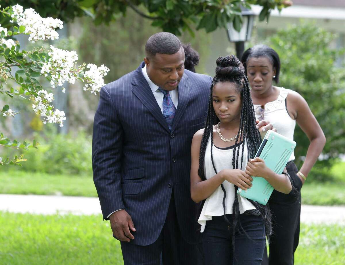 Quanell X leads Jada and an unidentified woman to the news conference on Thursday.
