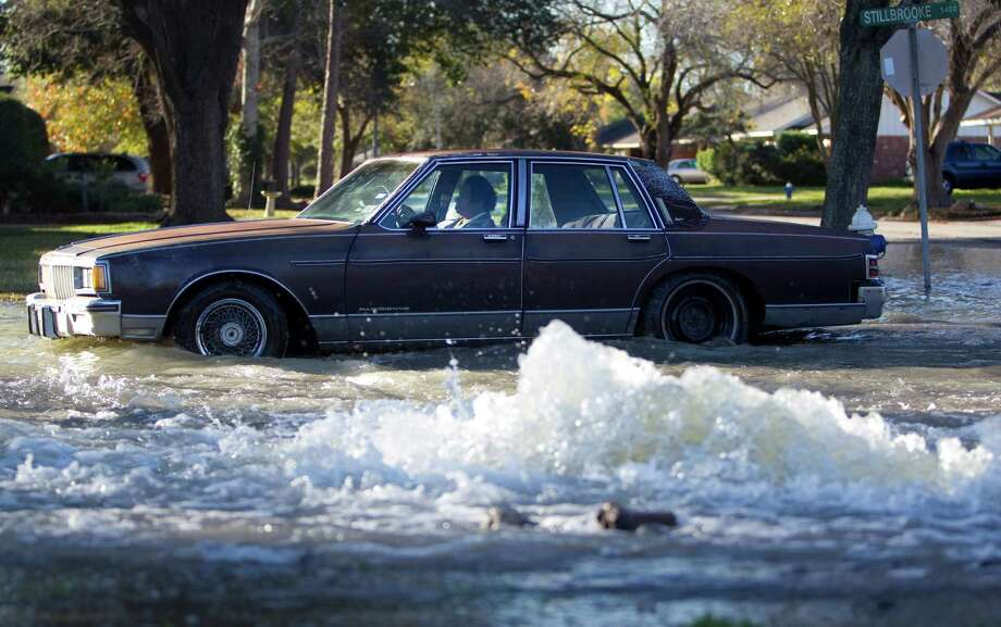 A car drives past a water main break on the corner of Oasis Dr. and Stillbrooke Dr. Monday, Jan. 2, 2012, in Houston. ( Johnny Hanson  / Houston Chronicle ) Photo: Johnny Hanson, Staff / © 2012  Houston Chronicle