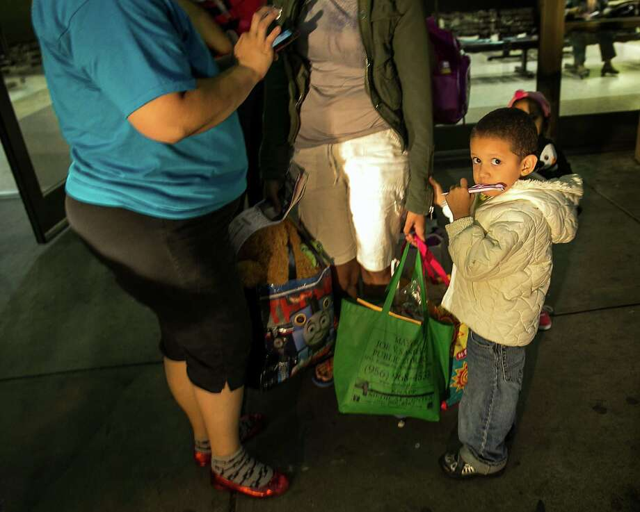 In this photo taken July 1, 2014, three-year-old Josefa, of Honduras, stands next to his mother, Eide Cerrato, center, as they prepare to board a bus leaving the city bus station in McAllen, Texas. About 90 Hondurans a day cross illegally from Mexico into the U.S. at the Rio Grande near McAllen, according to the Honduran Consulate, and the families are then brought to Central Station in McAllen and each is released on their own recognizance. Though most travelers have enough money to purchase their own bus tickets to meet family in cities across the U.S., many have nowhere to stay before the buses leave, and most are in need of rest, medical attention and sustenance. It falls to the local government and charities to welcome the uninvited visitors to America. Tens of thousands have also fled to the U.S. from El Salvador and Guatemala to escape violence.  (AP Photo/Austin American-Statesman, Rodolfo Gonzalez) Photo: Rodolfo Gonzalez, MBO / Austin American-Statesman