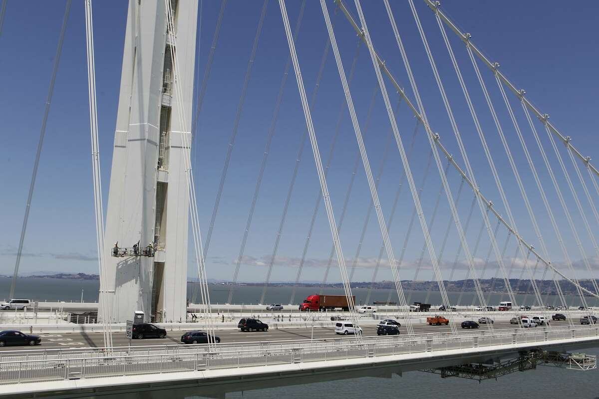Eastbound commuters drive past bridge crews repainting the SAS tower of the new eastern Bay Bridge span in San Francisco, Calif. on Thursday, July 10, 2014.