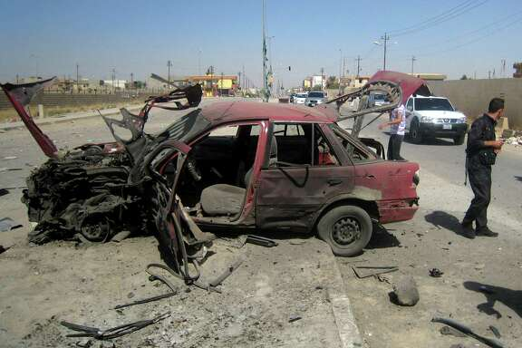 Iraqi citizens inspect the site of a car bomb attack Thursday on vehicles lined up at a gas station in the oil rich city of Kirkuk, 147 miles north of Baghdad.