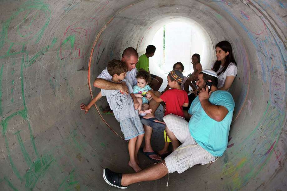 Israelis hide in a large concrete pipe used as a shelter during a Palestinian rocket attack Thursday on the southern Israeli village of Nitzan. The village is mainly inhabited by former Israeli settlers who left the Gaza Strip in 2005. Photo: MENAHEM KAHANA, Staff / AFP