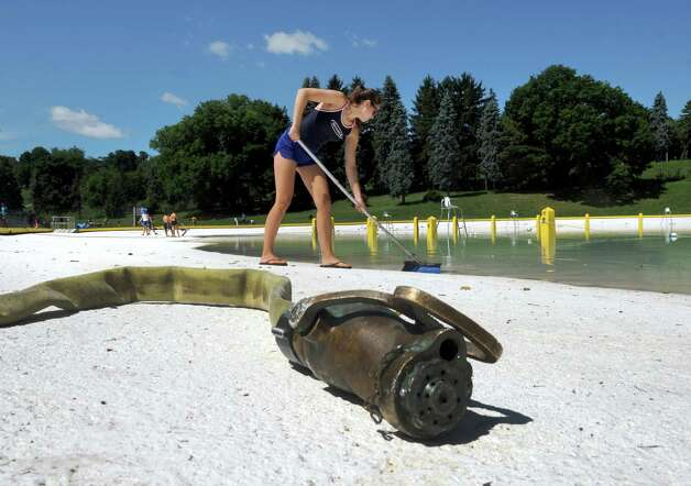 Lifeguard Maggie Driscoll works at cleang soot from the Lincoln Park pool following Wednesday night's rain storm Thursday morning, July 10, 2014, in Albany, N.Y. (Michael P. Farrell/Times Union) Photo: Michael P. Farrell / 00027735A