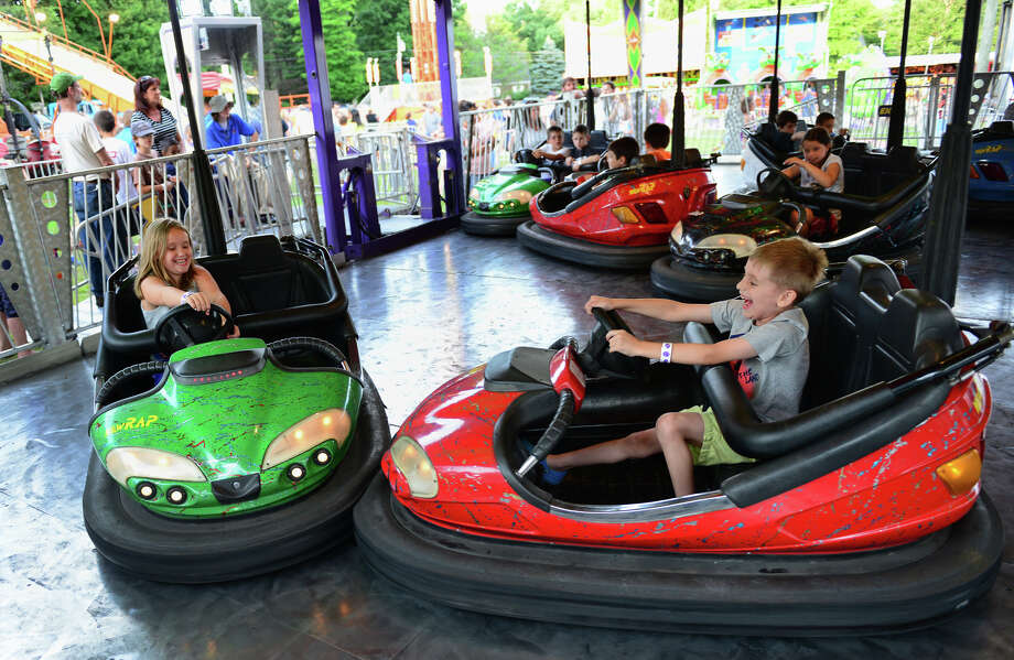 Isabella Roy, 9, of Monroe, and her brother William, 7, collide into each other as they ride the bumper cars, during the Monroe Fire Deparment Carnival at Fireman's Field in Monroe, Conn. on Thursday July 10, 2014. The carnival, located at the intersections of Route 110 and 111, continues through Saturday July 12th. Photo: Christian Abraham / Connecticut Post