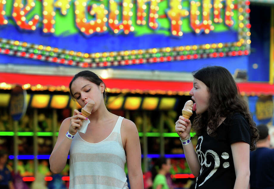 Sabrina Romansky, 15, of Monroe, and her friend Lindsey Wall, 15, right, both enjoy ice cream cones, during the Monroe Fire Deparment Carnival at Fireman's Field in Monroe, Conn. on Thursday July 10, 2014. The carnival, located at the intersections of Route 110 and 111, continues through Saturday July 12th. Photo: Christian Abraham / Connecticut Post
