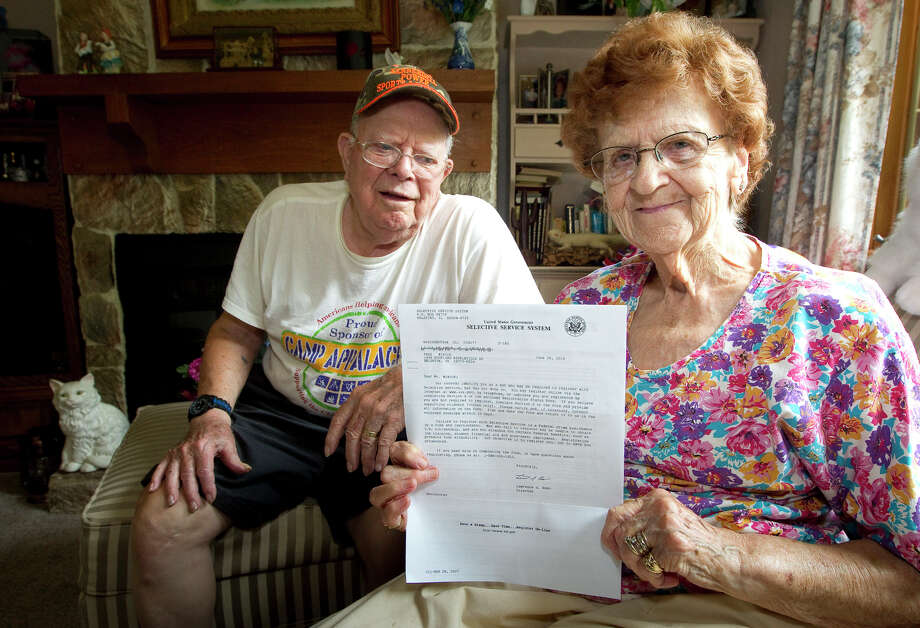 In this photo taken on Tuesday, July 8, 2014, Harold Weaver sits behind his wife, Martha, in their Nickleville, Pa, home. Martha holds a letter from the Selective Service for her late father, Fred Minnick, requiring him to register for the nation's military draft. The letter arrived too late for Minnick, who was born in 1894 and died on April 20, 1992. (AP Photo/The Derrick, Jerry Sowden) Photo: Jerry Sowden, MBR / The Derrick