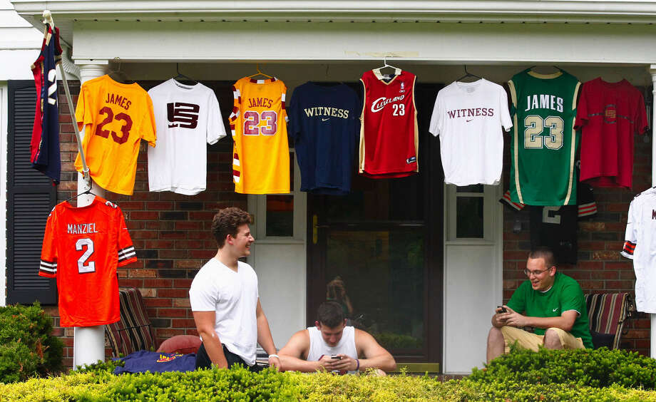 Joe D'Amico (from left), his brother Billy D'Amico and their friend Josh Heckman await the news of where LeBron James will play next year Thursday in Bath Township, Ohio. The D'Amicos are neighbors of James. Photo: Karen Schiely / Associated Press / Akron Beacon Journal